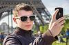 Junger Mann in Paris statt selfie vor Eiffel | Stock Foto