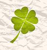 Klee mit vier Blättern auf zerknittertes Papier