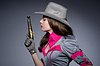 Woman cowgirl with gun in studio | Stock Foto