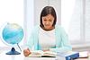 老师与地球和书籍在学校 | 免版税照片