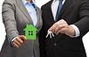 商人和商人拿着绿色的房子 | 免版税照片