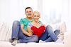 Glücklich lächelnde Paar mit roten Herzen zu Hause | Stock Photo