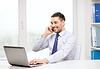 Biznesmen z laptopem i smartfonem w biurze | Stock Foto