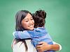 幸福的女人和小女孩拥抱在学校 | 免版税照片