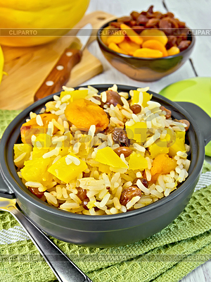 Fruit Pilaf with pumpkin, raisins, dried apricots in a black pan on a ...