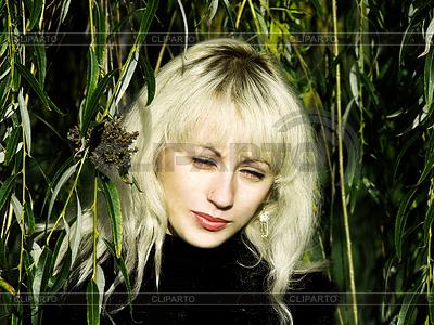 Ładna blondynka w zielonej zarośla wierzbowe | Foto stockowe wysokiej rozdzielczości |ID 4122849