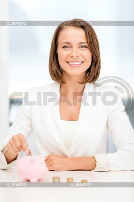 Geschäftsfrau, die Euro-Münzen in Sparschwein | Foto mit hoher Auflösung |ID 4456378