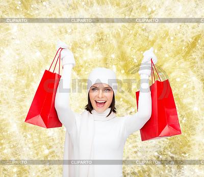 Smiling young woman with red shopping bags | Foto stockowe wysokiej rozdzielczości |ID 4483923